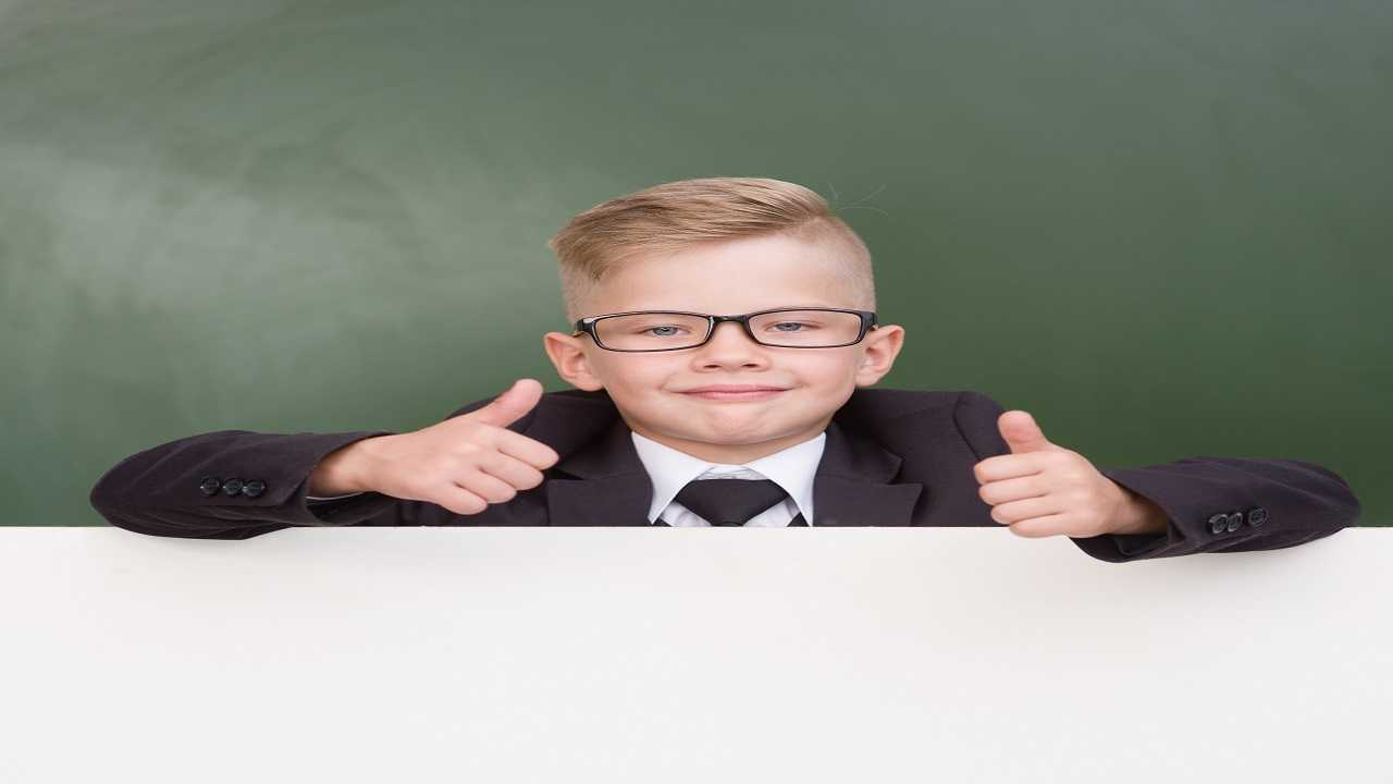 Boy in a business suit looks out from behind a banner and showing thumbs up.